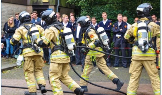 Brandweerlieden kijken toe hoe collega's het incident aanpakken.