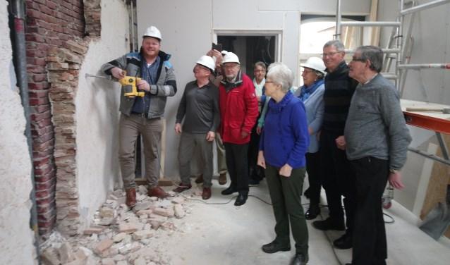 Wethouder Thomas Melisse sloopt de muur onder toeziend oog van bestuur en vrijwilligers. FOTO MONICA VERSLUIS