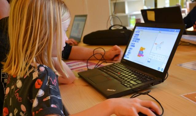 Noa (7) leert samen met haar vader hoe je moet programmeren FOTO REMKO VERMUNT