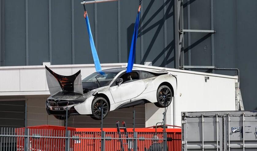 De peperdure elektrische sportauto wordt omhoog getakeld uit de blusbak