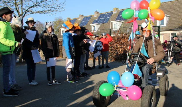 De jubilerende meester Alfons wordt feestelijk onthaald op het schoolplein.