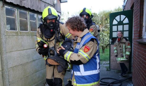 Kinderburgemeester Hessel helpt brandweerlieden een 'slachtoffer' in veiligheid te brengen.