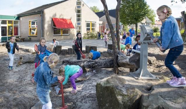 Op een groen schoolplein leren en ontdekken kinderen in de buitenlucht.