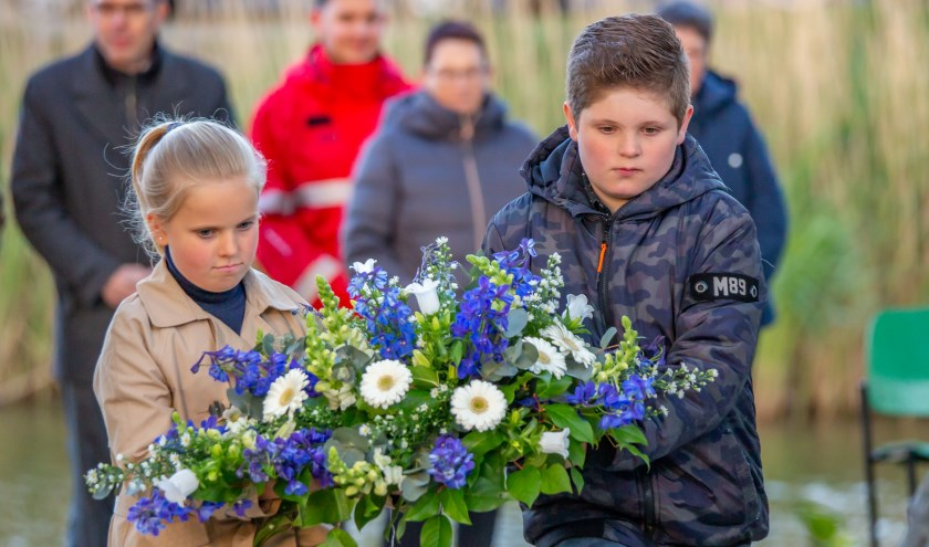 Twee kinderen leggen een bloemenkrans neer.
