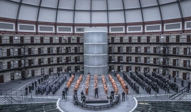 De gevangenisdirecteur spreekt de gevangenen toe.
