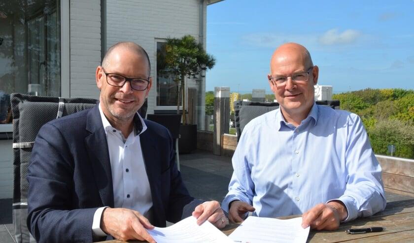 Jules van Leijden (l) van de Rabobank en Kustmarathon-voorzitter Chris Simons met het nieuwe contract.