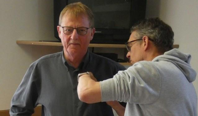 Erelid Dick Schinkel krijgt het speldje uitgereikt door PSR-voorzitter Alex Achterhuis.