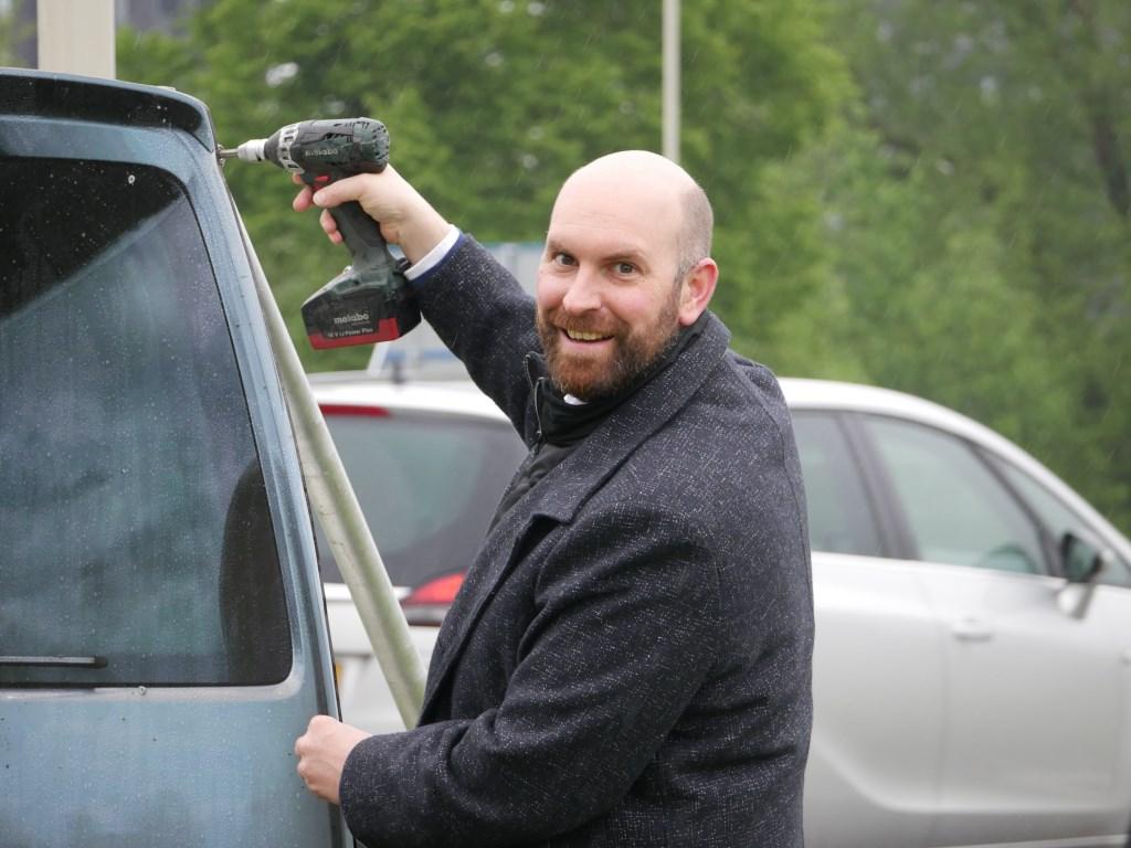Wethouder Boaz Adank bracht de laatste schroef aan voor het bord met het flitsbusje. Foto: Wesley van der Linde © BredaVandaag