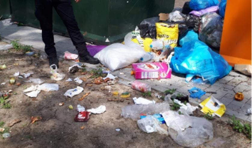 Er lag een enorme hoop afval naast de containers.