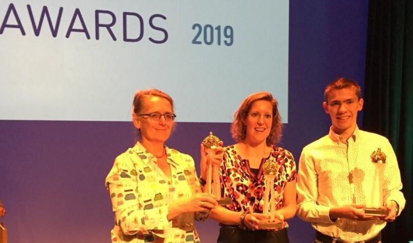 Een vertegenwoordiger van de Luisterlijn, Michelle Baas en Anderd van den Bosse met de Lange Jan Award.