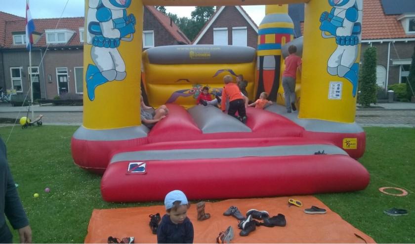Kinderen vermaken zich prima op het springkussen tijdens de buitenspeeldag.
