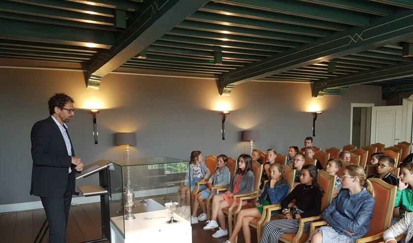 Stadsarchivaris Van den Kieboom vertelt de leerlingen over de beker.