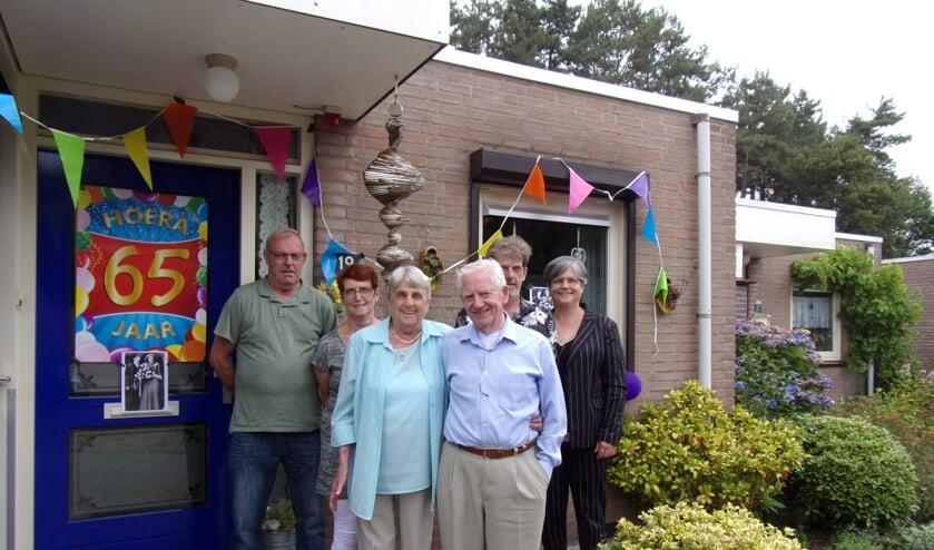 Jef en Virginia Scheffers bij hun vrolijk versierde voordeur, omringd door hun kinderen en aanhang.
