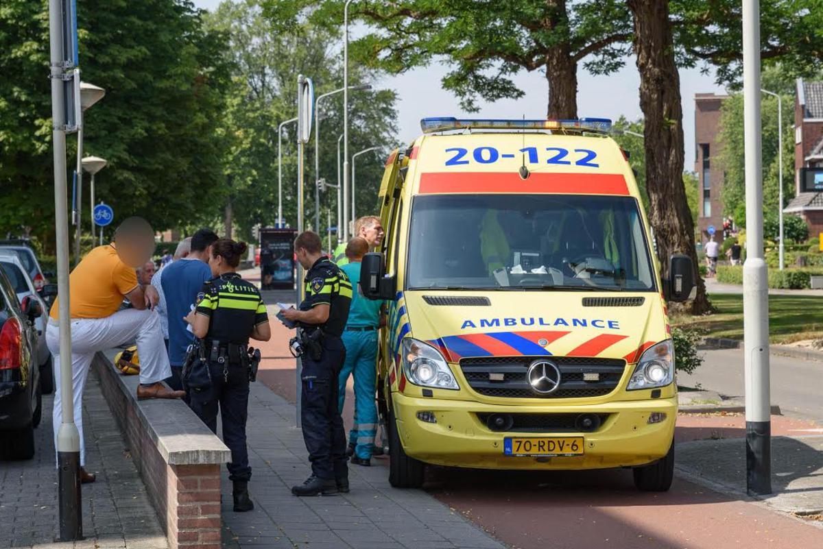 De ambulance zal de gewonde fietsster neer het ziekenhuis vervoeren.