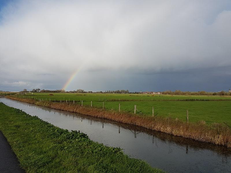 Buienwolk met regenboog boven de Haagse Beemden polder