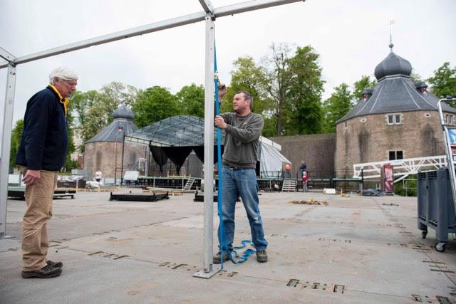 De festivaldirecteur kijkt toe hoe een medewerker een tent opbouwt