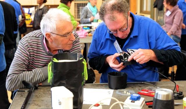 Eén van de vrijwilligers (rechts) buigt zich over een technisch mankement, tijdens de vorige editie van het Repair Café in het Science Centre. Zondag 5 februari wordt hier het 5-jarig jubileum gevierd. (foto: Koos Bommelé)