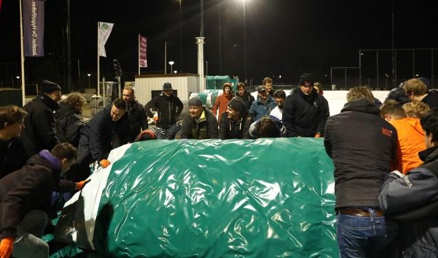 Vele handen maken donderdagavond licht werk, als vrijwilligers van Ring Pass een stukje blaashal opbouwen. Meer foto's staan op www.delftopzondag.nl.