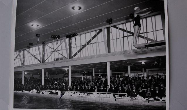 Een ouderwets mooie oude foto van de opening van het Sportfondsenbad Delft in 1936, toen mannen nog pakken en vrouwen nog badpakken droegen.