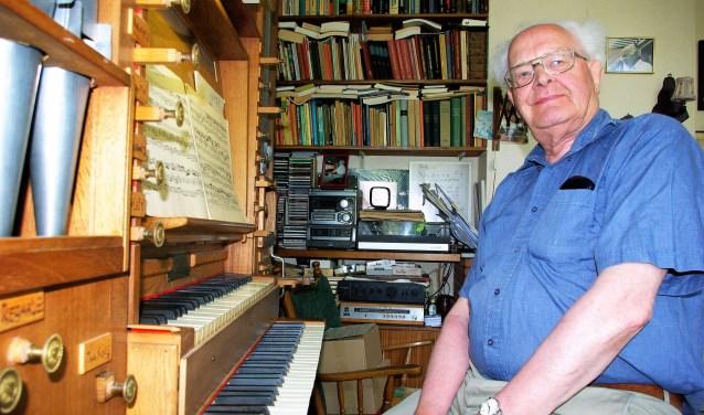 Jan J. van den Berg in zijn eigen woning, achter zijn zelfgebouwde orgel.