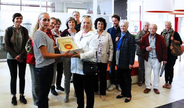 De bewoners hadden een 'niet-slopen-taart' meegenomen voor de medewerkers van Woonbron. (Foto: Koos Bommelé)