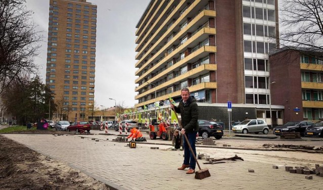 Ondernemer Martin Panis veegt, symbolisch, het laatste stukje van de nieuwe parkeerplaatsen in.