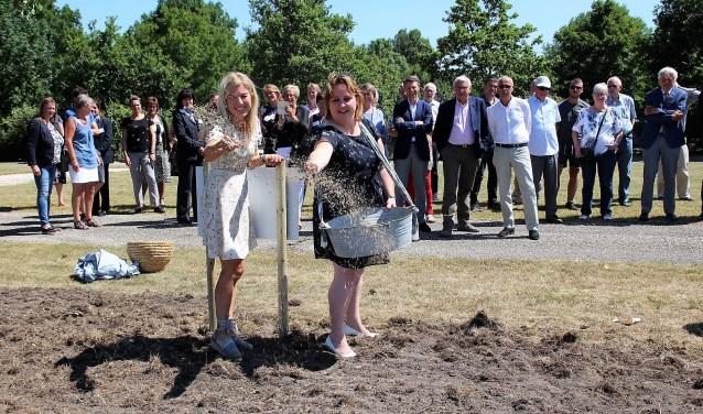 Deborah Post en wethouder Ilona Jense van de gemeente Pijnacker/Nootdorp strooien bloemzaad bij begraafplaats Sint Janshof