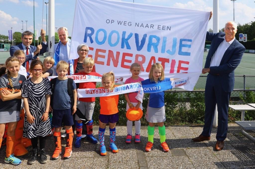 Voorzitter Peter van Haagen van Ring Pass showt, samen met de kleinste leden,vol trots de slogan. Ring Pass is de 1000e rookvrije sportvereniging in Nederland (Foto: Koos Bommelé)