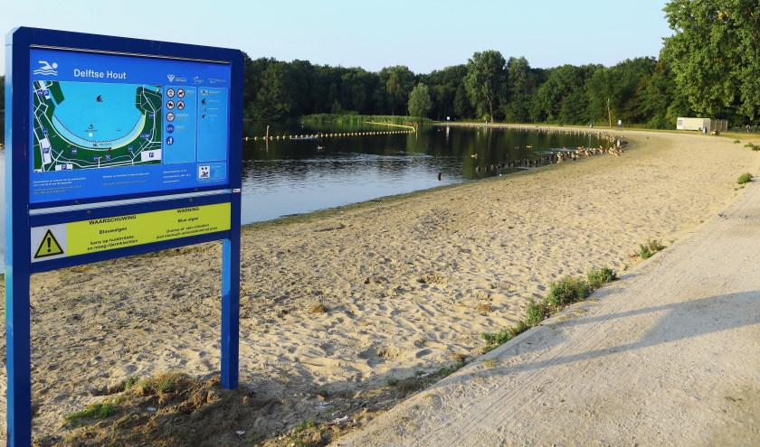 Het bord dat waarschuwt voor blauwalg in het water van De Delftse Hout