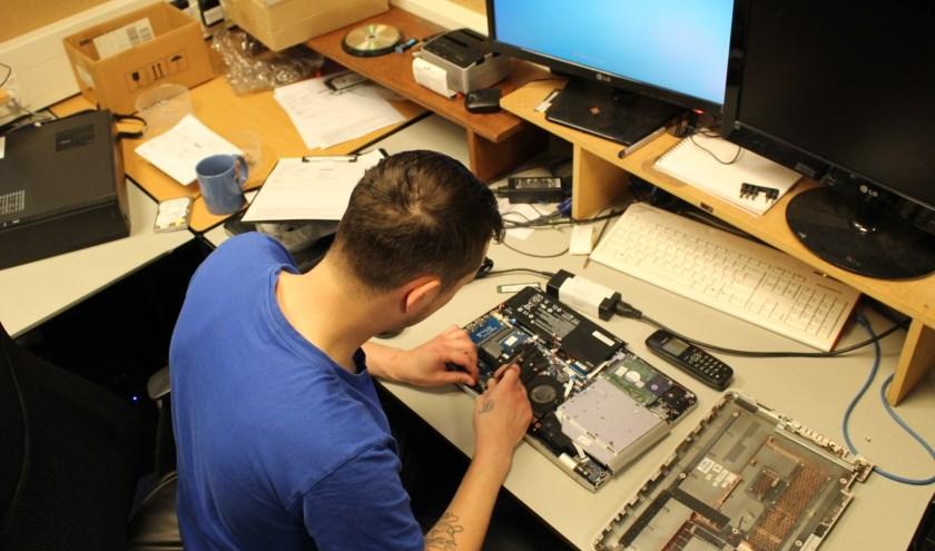 Rick is druk bezig met het repareren van een laptop. (Foto: EvE)