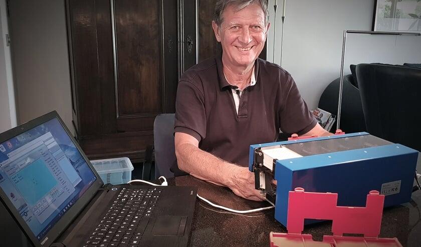 Peter Bommele, voorzitter van de Delftse bridgevereniging Gisolf bij een kaartdeelautomaat.