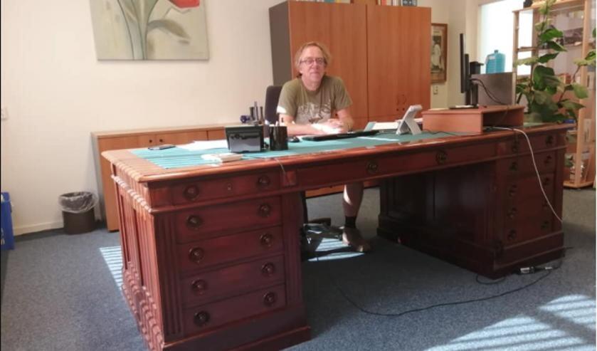 Jan van der Mast achter het imponerende bureau van zijn held Jacques van Marken