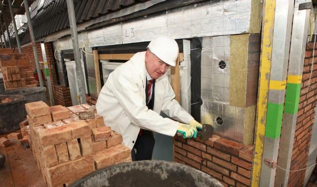 Met rasse schreden afgedaald uit zijn ivoren toren hanteert meneer Van der Velden met verve de troffel om zijn steentje bij te dragen aan de nieuwbouw aan de Jan Steenlaan.