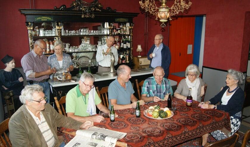 Een deel van de vrijwilligers die hebben bijgedragen aan de totstandkoming van het museumcafé poseren voor de historische tapkast