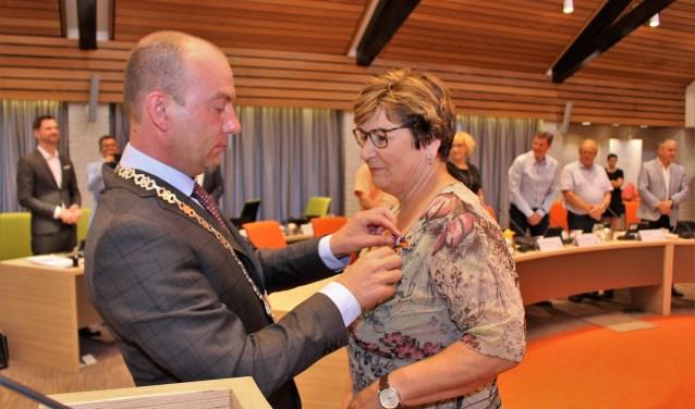 Burgemeester van Neerbos reikt de versierselen uit.