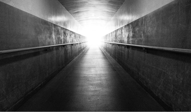 A long underground corridor leads up the the surface and the light at the end of the tunnel
