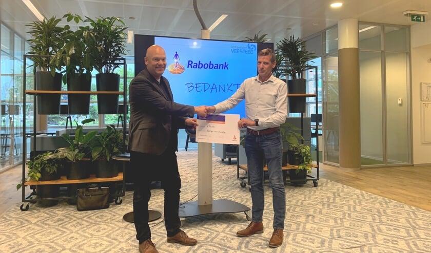 Cheque overhandiging van €10.000,- vuit handen van accountmanager MKB Paul Thonen van de Rabobank aan Kees Willems van camera werkgroep van Bedrijvenpark Veesteeg.