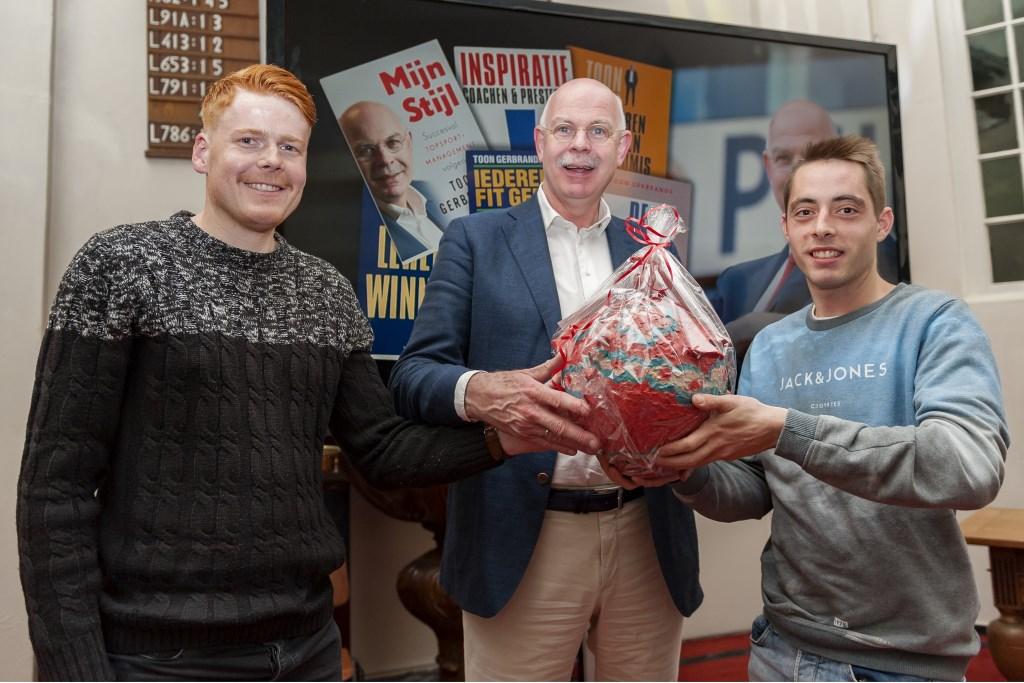 Twee jongens van het G-elftal van SV Budel geven een presentje aan Toon Gerbrands  Foto: Jos Meusen © grenskoerier