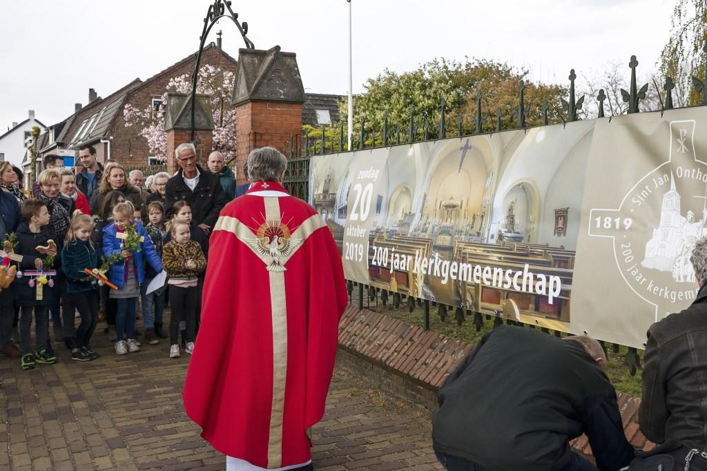 De onthulling van een grote banner aan het hek van de kerk.