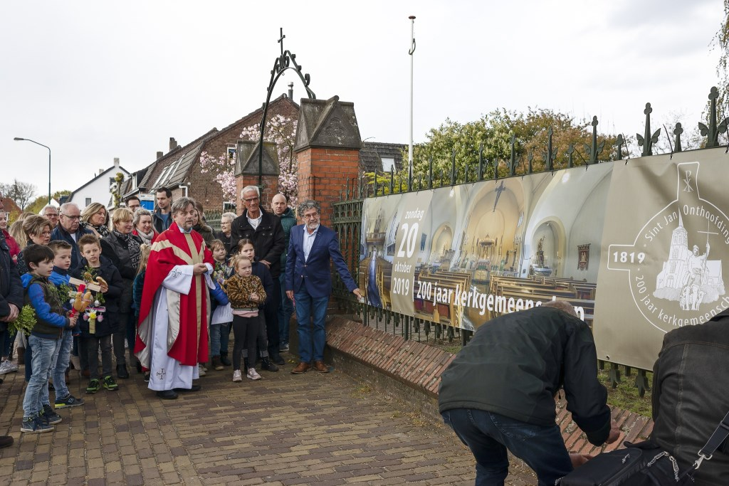 De onthulling van een grote banner aan het hek van de kerk. Foto: Gerard Staals © grenskoerier
