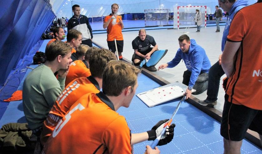 De spelers van De IJssel luisteren aandachtig naar de instructies van coach Mathieu de Jong. (archieffoto)