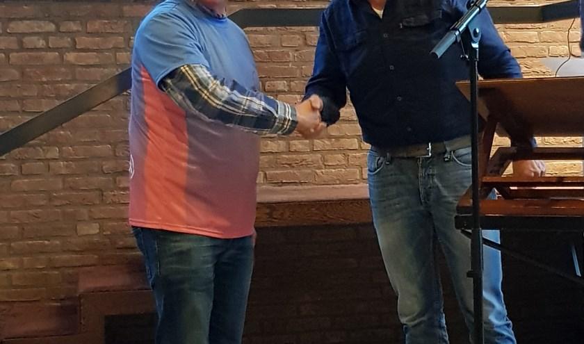 Koorlid Leendert Tanis (links) ontvangt een FietsJeMans-shirt uit handen van dirigent Martin Mans. (foto: pr)