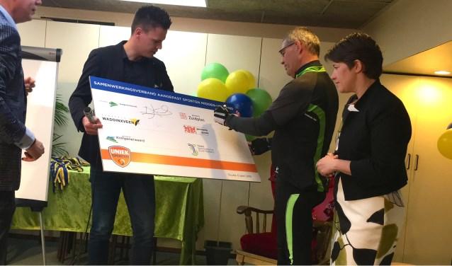 Wethouder Jan Verbeek tekent in sportieve outfit voor betere sportmogelijkheden voor mensen met een beperking.
