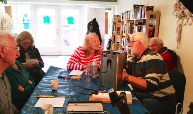 SAZ-klusser Nico de Weerd uit Nieuwerkerk doet zijn best om een espressomachine weer aan de praat te krijgen. (foto en tekst: Judith Rikken)