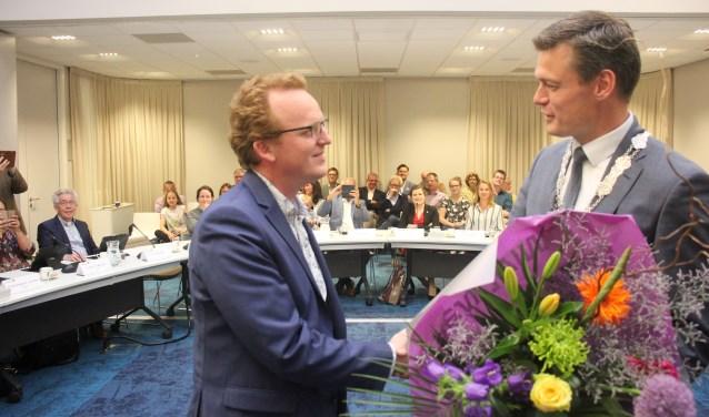 Erik Segers kreeg uit handen van burgemeester Nieuwenhuis een bos bloemen bij zijn vertrek als raadslid.