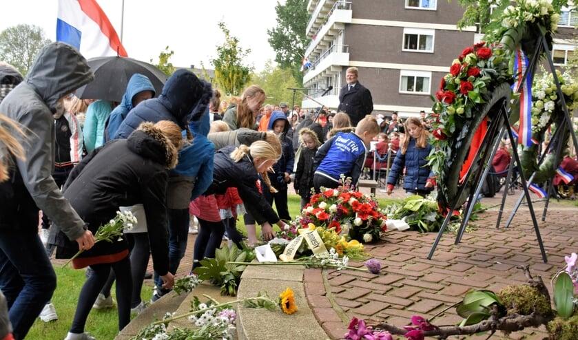 Bloemen werden bij het herdenkingsmonument neergelegd door leerlingen van het Coenecoop College. (foto en tekst: David Zandbergen)