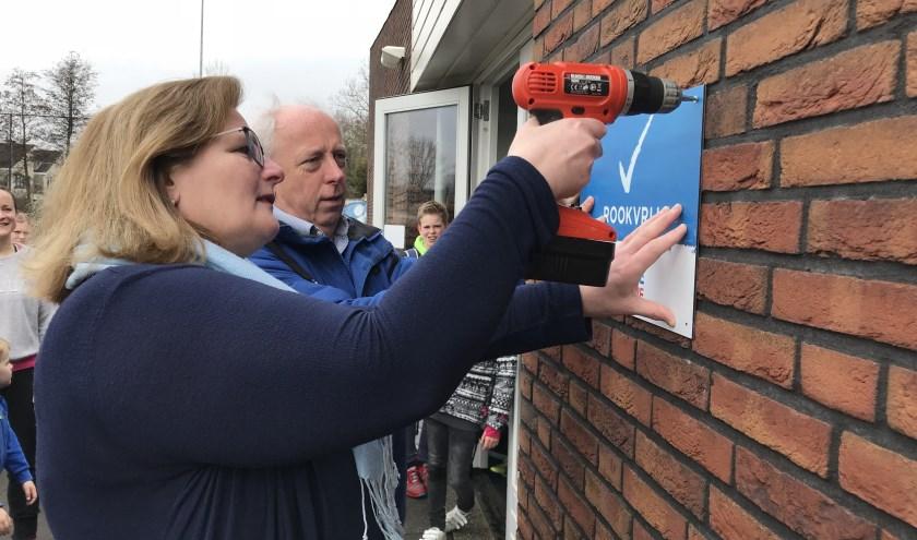 Toenmalig wethouder Brigitte Leferink schroefde in maart 2018 het rookvrij-bordje op de muur bij HCW. (foto: archief HvH)