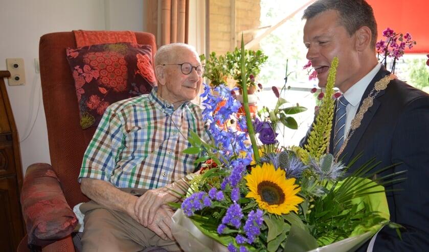 De 100-jarige Dirk van Rooijen kreeg van burgemeester Nieuwenhuis een bloemetje. (foto en tekst: Nicole Lamers)