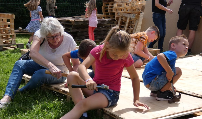 Oma helpt mee met het bouwen van een hut. (Foto en tekst: Annette van den Berg)