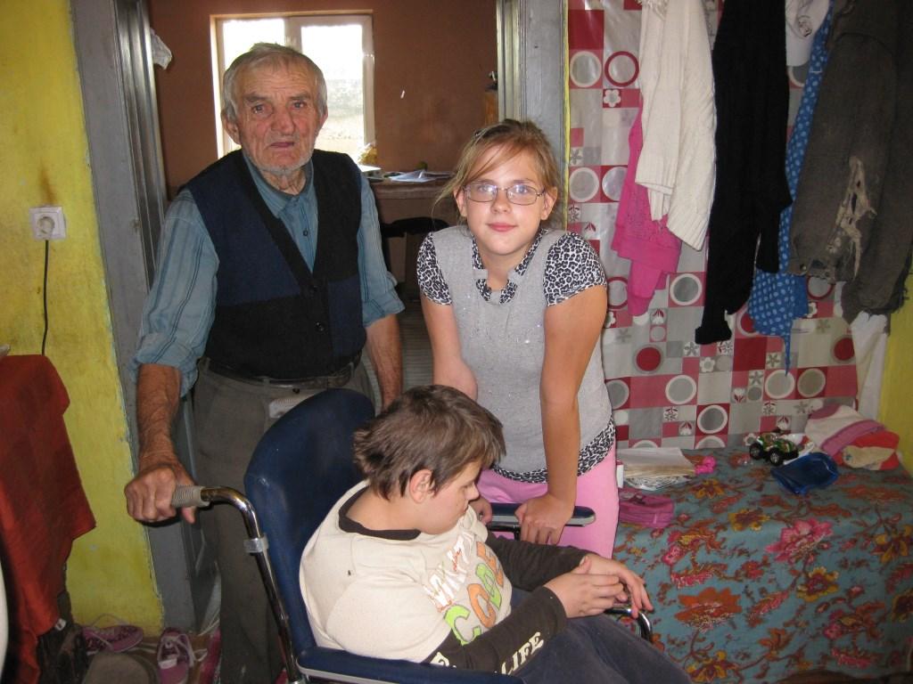Een tweeling met hun zorgende opa waaraan Vrienden van Salonta spullen levert, zoals de rolstoel voor het dubbelgehandicapte meisje (m.) (Foto: Stichting Vrienden van Salonta) Foto: Stichting Vrienden van Salonta © MooiBoxtel